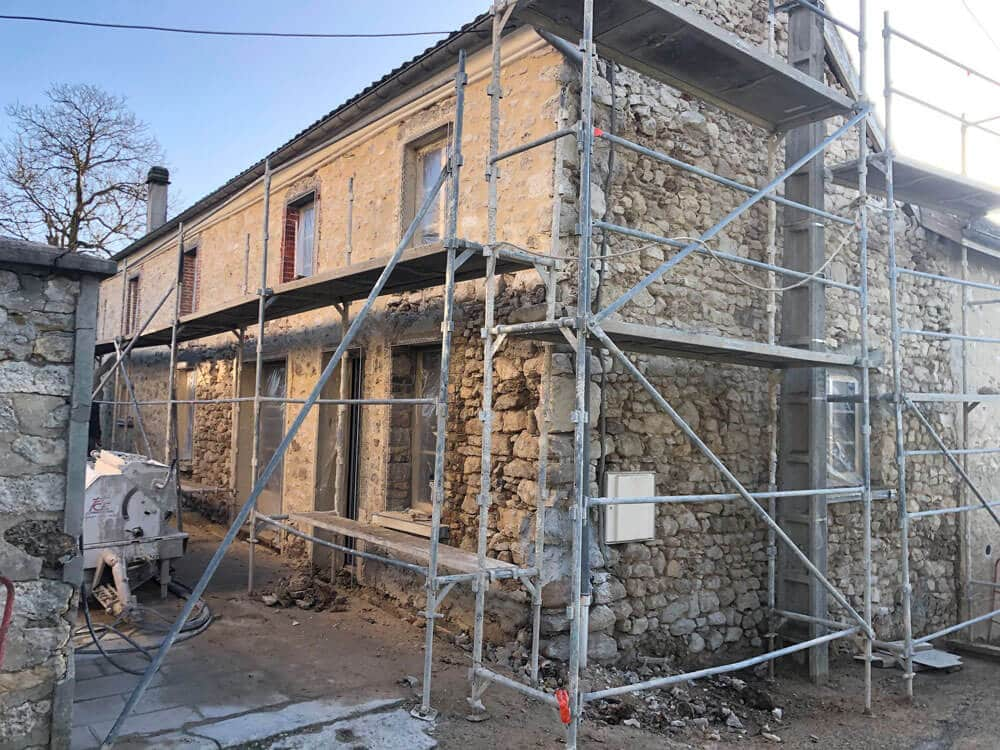 Décrépissage d'une maison en pierres apparentes